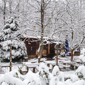 Winter in der Heidemühle, vom Schnee bedeckter Biergarten mit uriger Kaminbaude