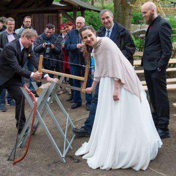 Brautpaar beim Holzsägen, Hochzeitsfeier