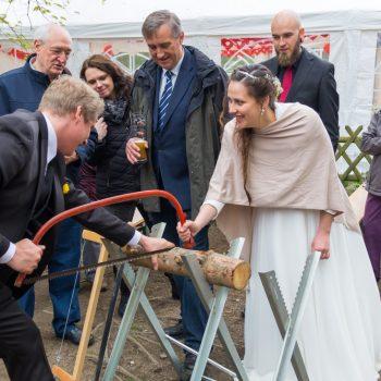 Brautpaar beim Holzsägen, rustikal Hochzeit feiern