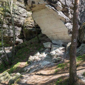 abgebrochener Fels, dem Wegzeichen schwarzer Pfeil folgend